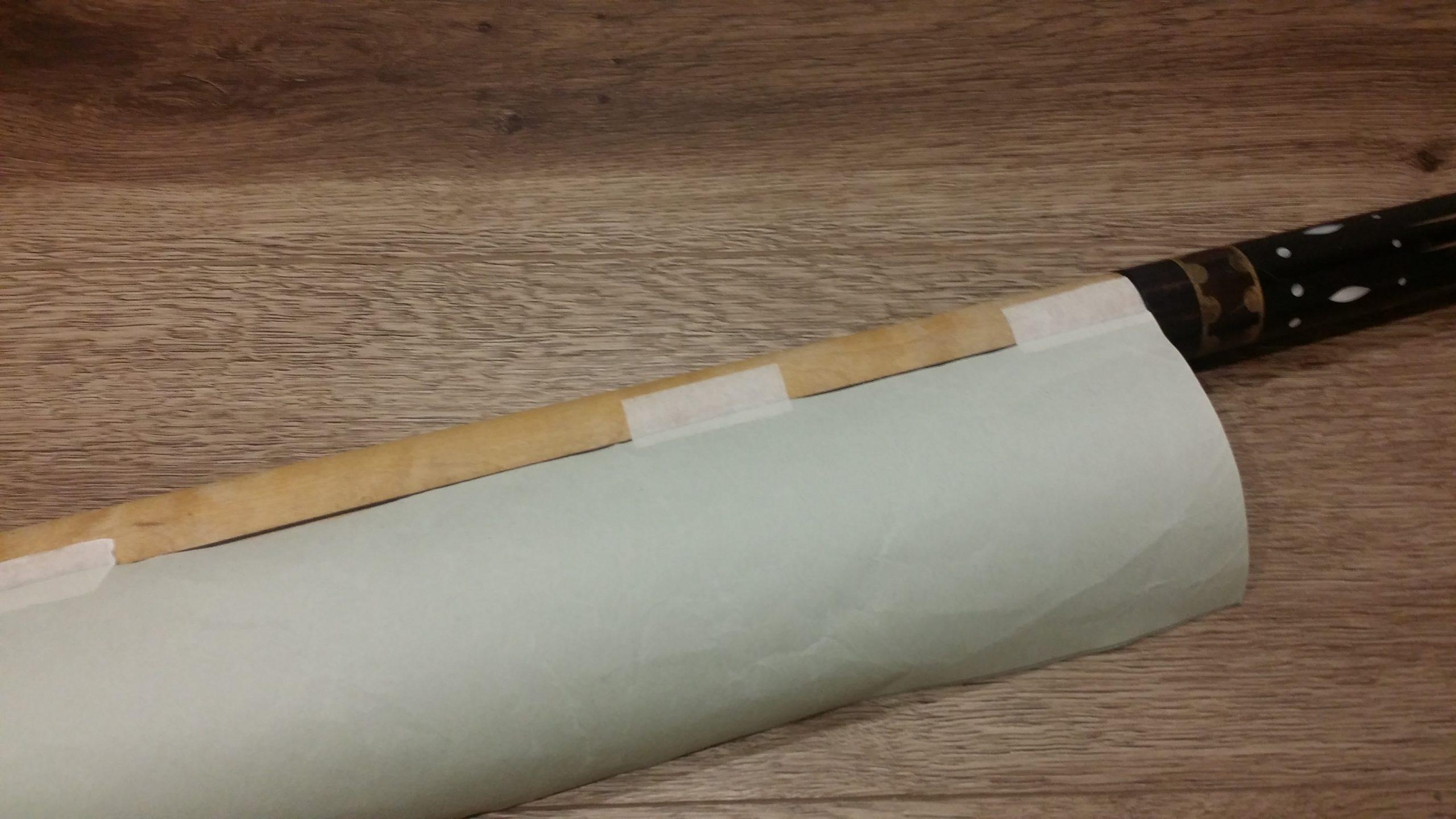 上側の横のラインをグリップ上部の境目に合わせ、縦のラインは中心線に合わせて、型紙をテープで固定